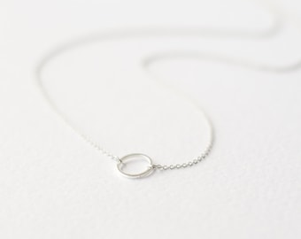 Geometric silver necklace with karma circle pendant