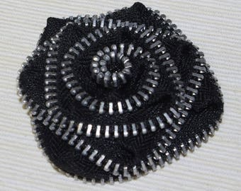 Black zip and metal flower brooch.
