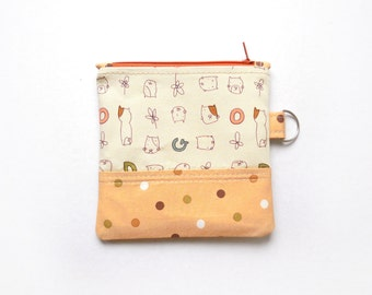 Small coin purse/zipper pouch in light brown with cute dogs and letters, with a darker brown accent and an orange zip