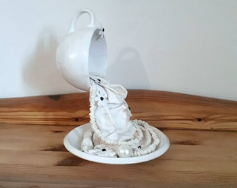 White cup and saucer. Floating cup. Home decor. Pearls. Shells.