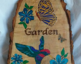 My Garden garden art wood burned and painted tree slice wedge with a butterfly, hummingbird and blue flowers.
