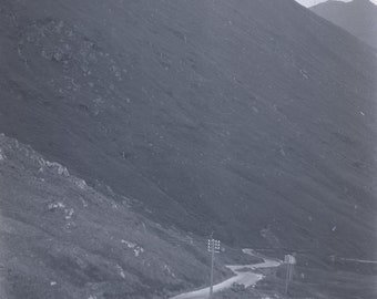 A black & white negative of a winding road in the mountains unknown location