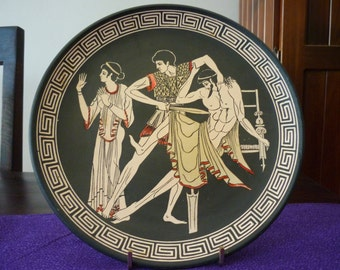 Grecian wall art. Decorative handmade plate with images of a Greek tragedy. Vintage design, kitsch home decor. Terracotta plate.