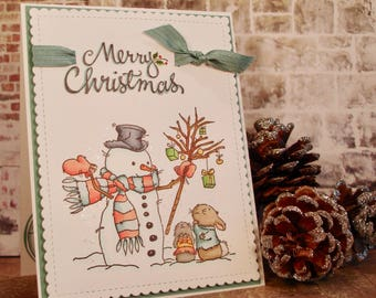 Handmade Christmas Card with hand stamped and colored image of snowman with rabbits, Merry Christmas, glitter snow, for friend or family