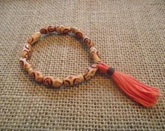 Patterned wood bead bracelet with coral tassel