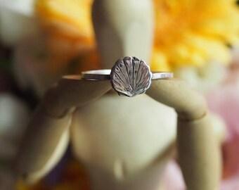 A super simple fine silver scallop shell on a square sterling silver ring.