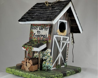 """Slanted Brown Barn Birdhouse , with sign """" Never too far to Grandma's """" , Wood Pile , Rope and Lots of Flowers"""