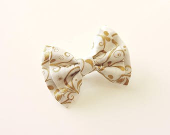 brooch white bow and Golden arabesques
