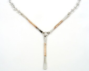 Wish bone shaped necklace made of three flat textured  sterling silver bars, wrapped with solid rose gold strap, held by a ring chain.