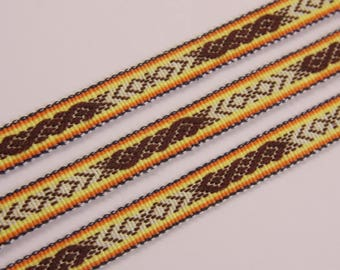 Ribbon, hand woven with ancient symbols. Colours - brown, white, yellow, orange, black.