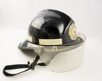 A Retired 1972 Fireman's Helmet - Black With Insignia - Mfg. by Cairns & Bros.- 660C Metro Firefighters Helmet - With Shield