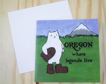 "CARD: ""Oregon Cat"" featuring a winking cat in a Sasquatch or Bigfoot costume, by Mt. Hood"
