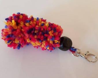 A handmade multi-coloured triple Pom Pom key ring complete with a dark bead.