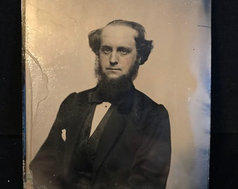 1/2 play tintype photograph of a bearded man.