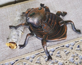 An ancient ashtray beetle. Metal stand for cigarettes of copper color. Stand for candles or jewelry. Decor for the table.