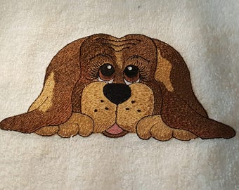 White terry cloth hand towel embroidered with a dog.