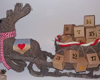 Advent calendar: reindeer Santa Claus and his sleigh with twigs and kraft boxes