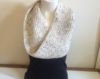 Egg colored infinity scarf with black, brown and grey spots.