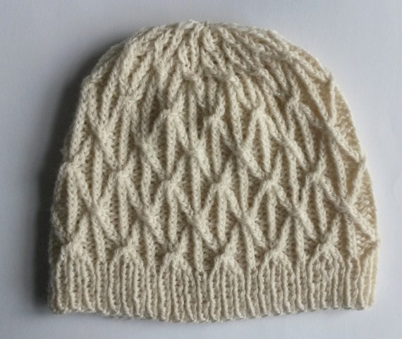 Aran Beanie Hat: handknitted in 100% wool. Original design. Made in Ireland. Aran cable pattern in traditional white/cream wool. Unisex.