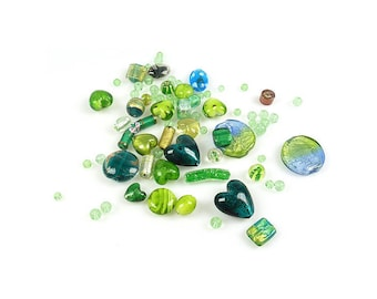 An assortment of green shaped glass beads variable.