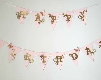 Happy birthday banner in gold with pink flags and pink butterflies. Woodland fairy, garden, enchanted fairy.