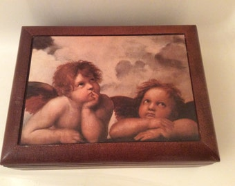 """A Wooden  Musical Jewelry Box with Two Angels on the Top, """"Love Story""""."""