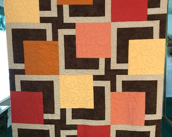 Modern quilt with rich earth tones --- browns, peach, orange, yellow fabric.