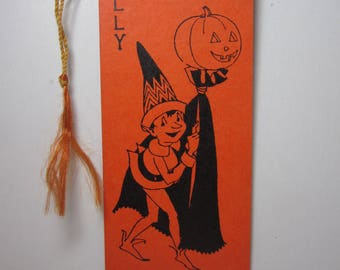 rt deco 1920's-30's bright orange colored Hallmark halloween bridge tally shows an pixie carrying a jack o'lantern on a stick with a cape