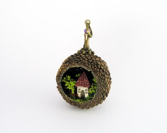Miniature world pendant. Tiny house amidst trees and flowering bushes in real acorn.