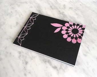 HANDMADE NOTEBOOK A6, Japanese stab-bound with pink cotton thread, 40 blank pink and blue pages, black cover, stencilled daisy pattern