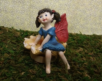 Resting Fairy Sitting On Her Yellow Daisy in the Fairy Garden