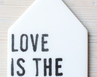 porcelain wall tag screenprinted text love is the answer.