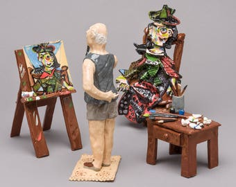 Artist Pablo Picasso out of hand built clay, working on his painting