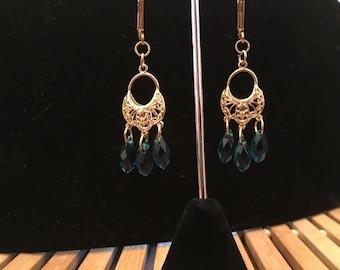 Earrings, dangle, beaded, peacock blue Swarovski crystals on a gold drop ear charm.