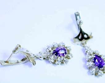 Earring with beautiful triangle stines and big purple stone in center.