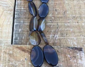 Oval banded black and brown Agate, 29mm x 17mm, 15 inch strand