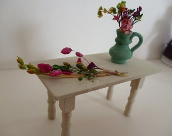 A shabby chic 24thscale table with flowers and a vase with flowers.