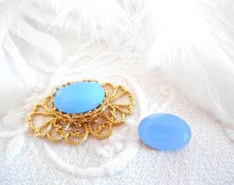 A cabochon 10 x 14 mm oval blue Opal crystal.