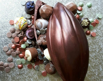 Cocoa pod filled with truffles. Made with dark chocolate, filled with buttons and handmade chocolate truffles. Including champagne truffles.