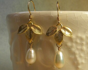 Classy gold plated leaves and lustrous white pear shaped pearls dangle earrings