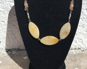 Oval shaped yellow natural stone with hematite.