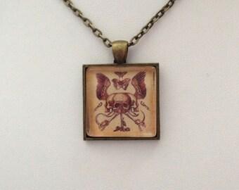 Danse Macabre Memento Mori Winged Skull One Inch Square Pendant in Antique Brass