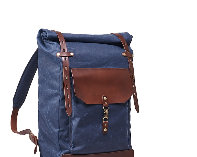 Roll top waxed canvas leather backpack. Navy blue and brown bag.