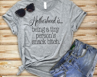 Graphic tee, funny t-shirt, funny t shirt, funny sayings, Motherhood is...being a tiny person's snack bitch™ brand shirt.