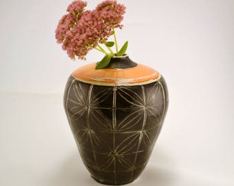 Porcelain soda fired black and orange vase, soda-fired, carved flowers on black slip