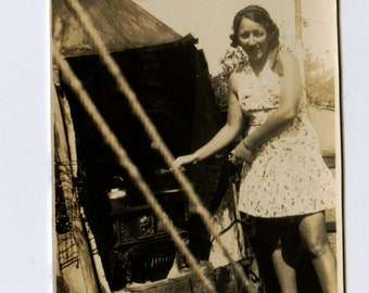 vintage 1930s snapshot photograph of a young girl cooking on an outdoor kitchen - camping or great depression