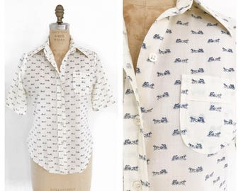 Cream short sleeve fitted blouse with horse and carriage print. Size S.