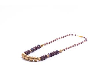 Purple and gold beaded necklace on rosary chain