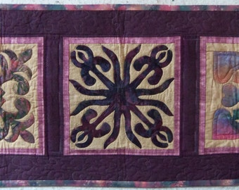 """This 22 1/2"""" X 58"""" wall hanging or table runner, is primarily purple with three different applique blocks."""