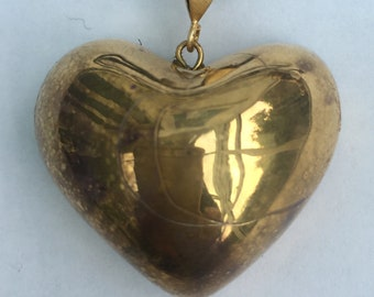 Gold heart pendant on an adjustable leather thong.